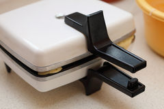 Waffle iron preparing waffles in kitchen stock images