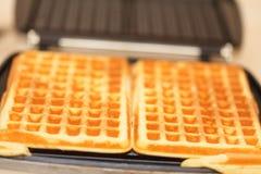 Waffle iron preparing waffles in kitchen Stock Photography