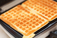 Waffle iron preparing waffles in kitchen Stock Photo