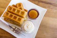 Waffle with maple syrup. And fresh milk cream royalty free stock photography