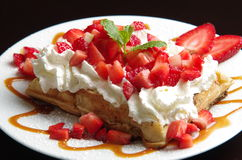 Waffle with mashmallows, whipped cream and strawberry Royalty Free Stock Images