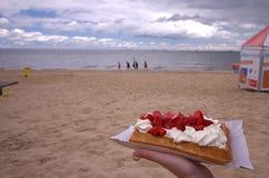 Waffle mit Erdbeeren und Creme auf dem Strand Stockfoto