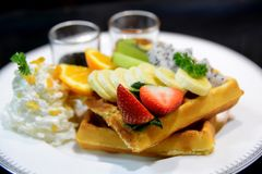 Waffle with mix fruit  and whipping cream  on a white plate Royalty Free Stock Photo