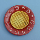 Waffle on red plate with hearts. Blueberry waffle on red plate with hearts Royalty Free Stock Images
