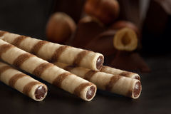 Waffle rolls with chocolate cream. On a dark background with nuts Royalty Free Stock Image