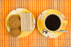 Waffle slice and coffee. Close-up waffle slice and cup with coffee on bamboo table-cloth Royalty Free Stock Photos