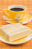 Waffle slice and cup with coffee. Close-up waffle slice and cup with coffee on bamboo table-cloth Royalty Free Stock Image