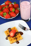 Waffle with strawberry and chocolate and a milkshake. Close-up of a waffle with strawberry and chocolate sauce served on a white porcelain plate with fork over a Stock Photos