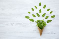 Waffle sweet cone with mint leaves on a white wooden background, top view. Flat lay, overhead. Summer background. Copy space stock photo