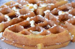 Waffle. A toasty brown waffle with melted butter powdered sugar and maple syrup for breakfast royalty free stock photo