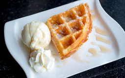 Waffle and vanilla ice cream two scoops and maple syrup. Popular sweets and dessert. sweet, fat and high calories. image for background, wallpaper, copy space royalty free stock photo