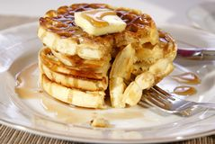 Waffles. Stack of fresh cooked breakfast waffles with butter and syrup being eaten with fork Royalty Free Stock Image