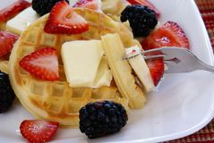 Waffles. Close up of Waffles with strawberries, blackberries, bananas, butter, and light vanilla syrup Stock Image