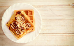 Waffles with banana and chcolate Stock Images