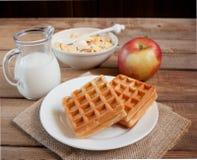 Waffles with banana, muesli, apple and milk jug Stock Images