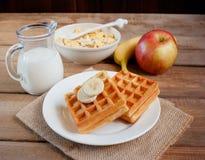 Waffles with banana, muesli and milk jug Royalty Free Stock Photos