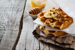 Waffles with banana and nuts honey. Rustic wood background Royalty Free Stock Photos