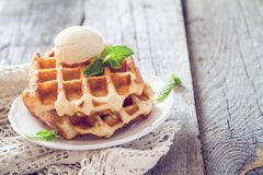 Waffles with banana and nuts honey. Rustic wood background, toned Stock Images