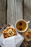 Waffles with banana and nuts honey. Rustic wood background, top view Stock Photos