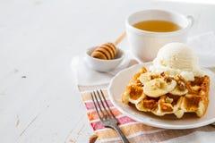 Waffles with banana and nuts honey. White wood background Stock Image