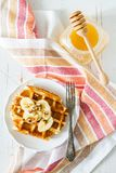 Waffles with banana and nuts honey. White wood background, top view Stock Photo
