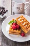 Waffles belgas com as framboesas, cobertas com mel em um de madeira Imagem de Stock Royalty Free