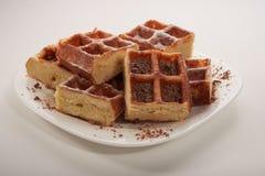 Waffles belgas com chocolate e crosta de gelo raspados em uma placa branca Foto de Stock Royalty Free
