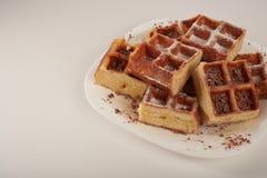 Waffles belgas com chocolate e crosta de gelo raspados em uma placa branca Foto de Stock