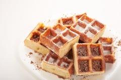 Waffles belgas com chocolate e crosta de gelo raspados em uma placa branca Imagem de Stock
