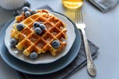 Waffles belgas com mirtilos e mel no fundo de madeira cinzento Foco seletivo do café da manhã saudável caseiro fotografia de stock royalty free