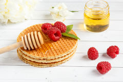 Waffles belgas finos com mel e framboesas Flores do jasmim e um frasco do mel em um fundo de madeira claro Imagens de Stock