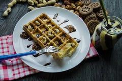 Waffles belgas tradicionais cobertos com o chocolate em um fundo de madeira escuro Café da manhã saboroso decorado com porcas dif fotos de stock