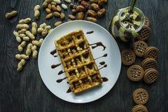 Waffles belgas tradicionais cobertos no chocolate em um fundo de madeira escuro Pequeno almo?o saboroso Decorado com porcas do ra imagens de stock royalty free