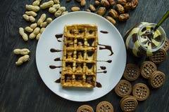 Waffles belgas tradicionais cobertos no chocolate em um fundo de madeira escuro Pequeno almo?o saboroso Decorado com porcas do ra imagens de stock