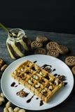Waffles belgas tradicionais cobertos no chocolate em um fundo de madeira escuro Pequeno almo?o saboroso Decorado com porcas do ra foto de stock royalty free