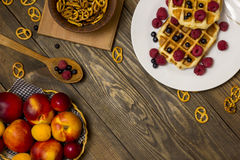 Waffles with berries and biscuits on the table, top view. Belgian waffles with berries on the table top view Royalty Free Stock Image