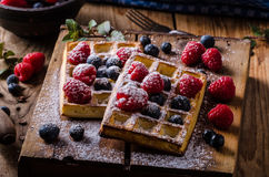 Waffles with berries. Blueberries, raspberries, topped with sugar, vintage styled photo Royalty Free Stock Photography