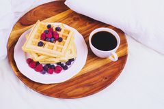 Waffles with berries and coffee on a wooden tray in bed, concept of breakfast in bed Stock Photo