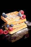 Waffles with berries isolated on black. Delicious waffles with blueberries, raspberries and blackberries on black background. Luxurious dessert background Stock Photography