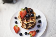 Waffles and berries on plate Stock Photography