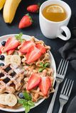 Waffles with berry fruit and cup of green tea Royalty Free Stock Photography