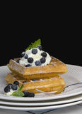 Waffles with Blueberries. Belgium waffles topped with whipped cream, fresh blueberries and dusted with confectioners sugar royalty free stock photos