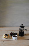 Waffles, cherry and french press coffee on the wooden table Royalty Free Stock Photos