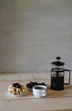 Waffles, cherry and french press coffee on the wooden table Stock Image