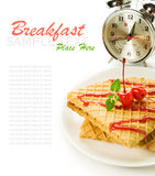 Waffles with cherry topping and alarm clock isolated on white Royalty Free Stock Photo