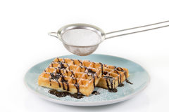 Waffles with chocolate on a blueish plate. Some powdered sugar i. S falling through a strainer stock image