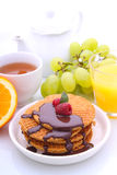 Waffles with chocolate and raspberries, grapes, tea and orange juice. Weekend breakfast: waffles with chocolate and raspberries, grapes, tea and orange juice stock images