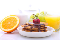 Waffles with chocolate and raspberries, grapes, tea and orange juice. Weekend breakfast: waffles with chocolate and raspberries, grapes, tea and orange juice stock photo