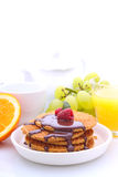 Waffles with chocolate and raspberries, grapes, tea and orange juice. Weekend breakfast: waffles with chocolate and raspberries, grapes, tea and orange juice royalty free stock image
