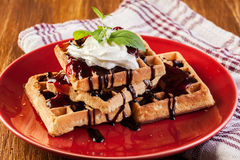 Waffles with chocolate sauce, whipped cream and confiture Royalty Free Stock Photos